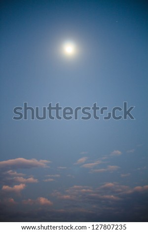 Romantic full moon rise during sunset in the evening sky - stock photo