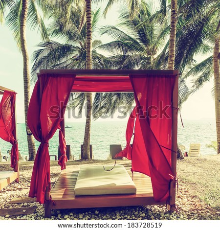 Romantic gazebo lounge at tropical resort. Beach beds among palm trees. Filtered image - stock photo