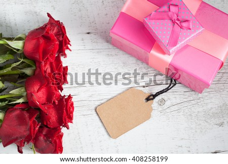 Romantic gift concept with red roses, gift boxes, and empty tag on white rustic wooden table. Top view with copy space. - stock photo