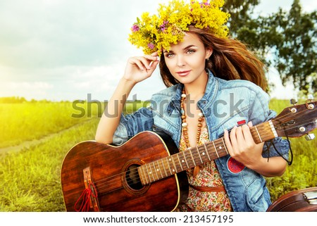 Romantic girl in a wreath of wild flowers playing her guitar. Summer. Hippie style.  - stock photo