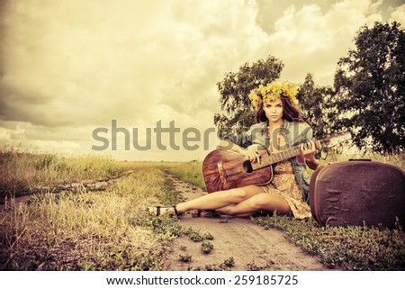 Romantic girl in a wreath of wild flowers travelling with her guitar. Summer. Hippie style.  - stock photo
