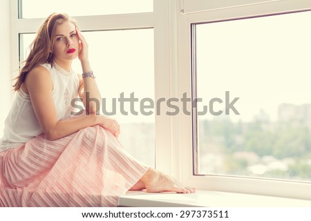 Romantic girl in long gown sitting by the window. Retro toned - stock photo
