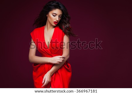 Romantic girl in red dress over burgundy background - stock photo