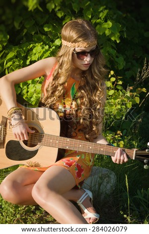 Romantic girl traveling with her guitar. Hippie style. - stock photo