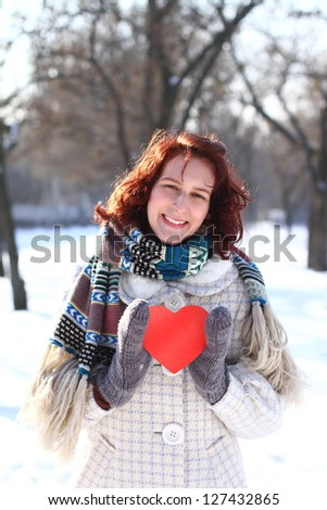 Romantic girl with a red heart in winter park - stock photo