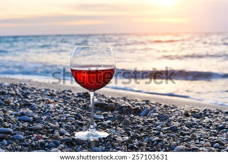 Romantic glass of wine sitting on the beach at colorful sunset, Glass of red wine against sunset, red wine on the sea ocean beach, sky background with clouds - stock photo