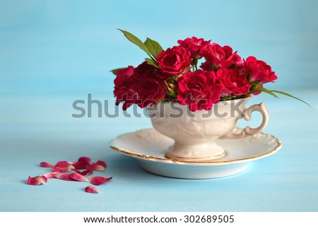 Romantic greeting card: Roses in porcelain cup on blue background - stock photo