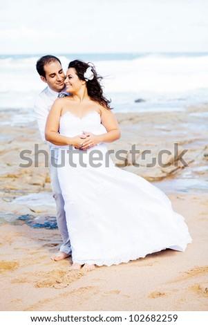 romantic groom and bride portrait on beach - stock photo