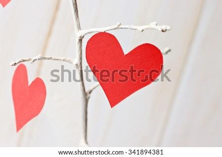 Romantic handmade valentines day decoration. Paper hearts symbols on tree twigs. Love Theme. White empty space. - stock photo