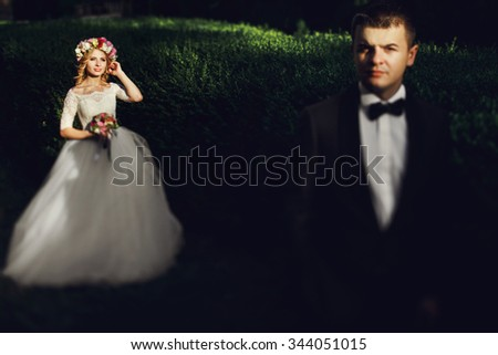 Romantic handsome groom in suit posing with gorgeous young bride at sunset in park - stock photo