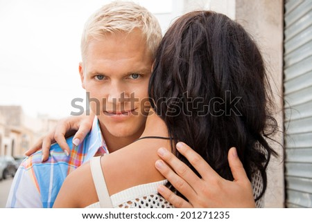 Romantic handsome young blond man hugging his girlfriend looking past the side of her head at the camera with a smile