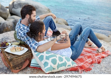 Romantic, happy couple during a picnic on the rocks, near the ocean - stock photo
