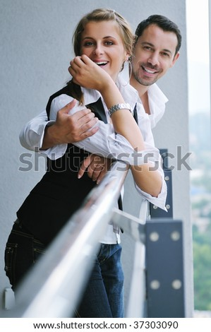 romantic happy couple relax and have fun at balcony in their new home apartment - stock photo