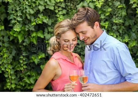 Romantic happy couple toasting wineglasses at front yard - stock photo