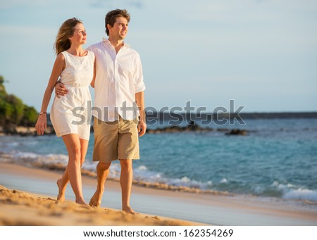 Romantic happy couple walking on beach at sunset. Smiling with arms around each other. Man and woman in love - stock photo