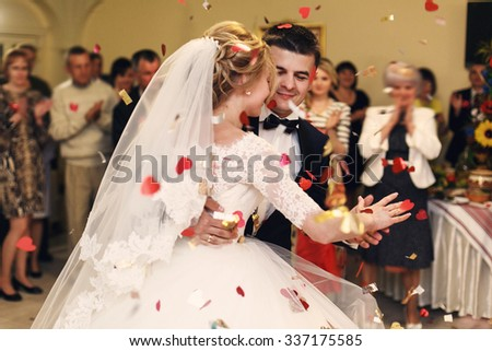 Romantic happy elegant groom in black suit and beautiful white dress bride first dance and rose petals closeup - stock photo