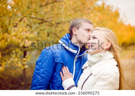 Romantic happy teen couple walking outdoors on cold autumn day - stock photo