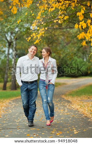 Romantic happy young beautiful couple on autumn walk. Vertical view - stock photo