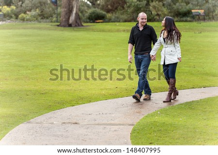 Romantic happy young couple holding hands walking in a beautiful garden path - stock photo