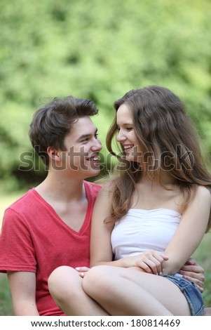 Romantic happy young teenage couple sitting on the grass in a park laughing as they look into each others eyes - stock photo