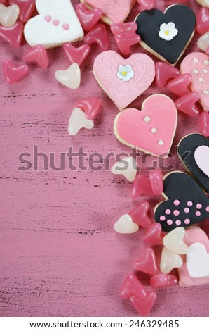 Romantic heart shape pink, white and black cookies and candy background on vintage shabby chic pink wood table with copy space, overhead vertical.