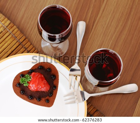 Romantic heart shaped chocolate cake with a strawberry on top. - stock photo