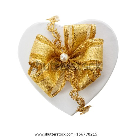 Romantic heart shaped gift and gold bow fastened with a pearl and braid for a loved one or sweetheart on Christmas, Valentines, birthday or an anniversary, overhead isolated on white - stock photo