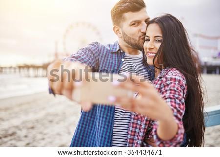 romantic hispanic couple taking selfie in front of santa monica - stock photo