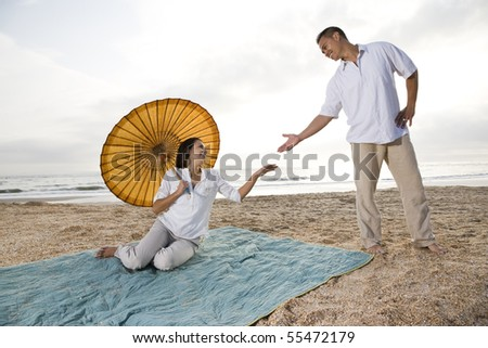 Romantic Hispanic couple together on beach - stock photo
