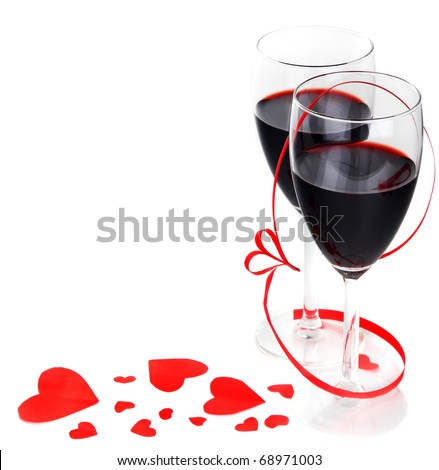 Romantic holiday drink, celebration of valentine's day, red wine with hearts ornament & ribbon decoration, isolated on white background - stock photo