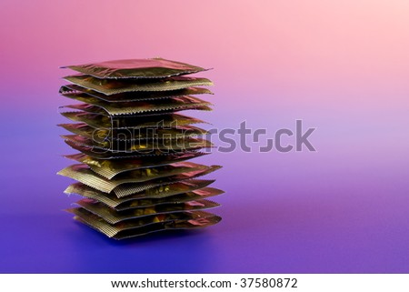 Romantic holidays - stack of condoms in pink lighting - stock photo