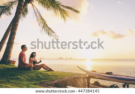Romantic holidays. Youth and vacation. Young loving couple drinking beer together while resting on the sea beach enjoying sunset.