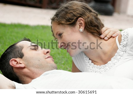 romantic image of beautiful couple smiling at each other laying on the grass in the park - stock photo