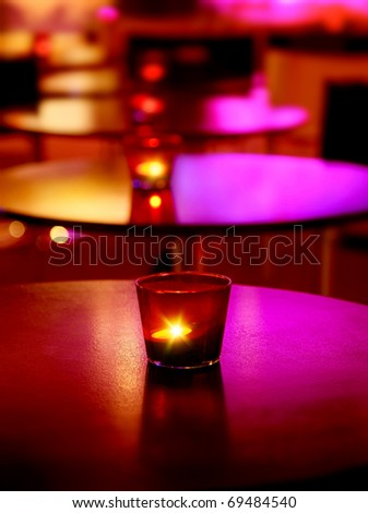 Romantic interior of a luxury restaurant with warm cozy candlelight - stock photo