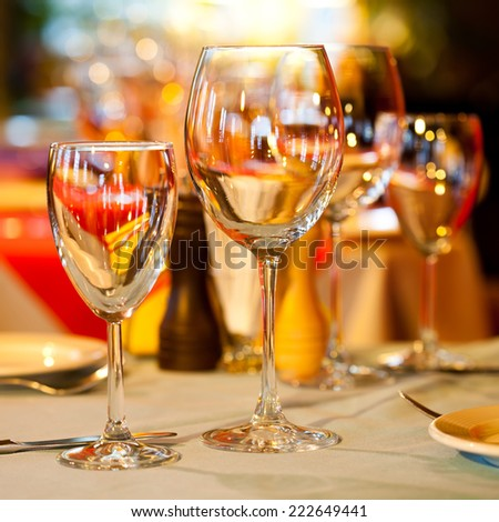 Romantic interior. Table in a restaurant with a bright tablecloth, napkins, wine glasses and cutlery. - stock photo