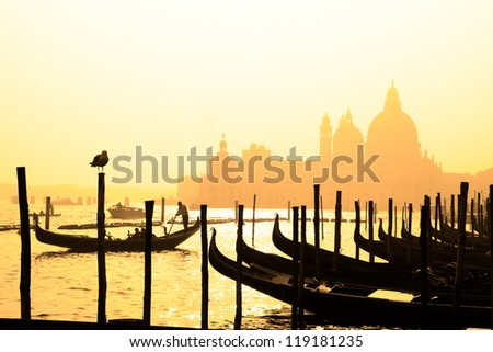 Romantic Italian city of Venice (Venezia), a World Heritage Site: traditional Venetian wooden boats, gondolier and Roman Catholic church Basilica di Santa Maria della Salute in the misty background. - stock photo