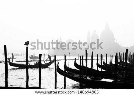 Romantic Italian city of Venice (Venezia), a World Heritage Site: traditional Venetian wooden boats, gondolier and Roman Catholic church Basilica di Santa Maria della Salute in the misty background. - stock photo