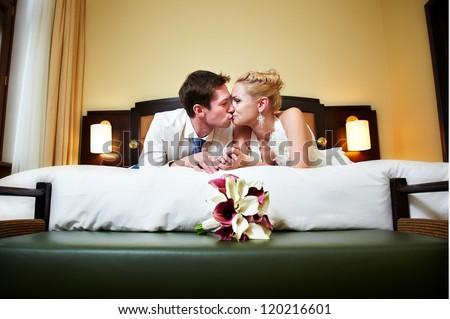 Romantic kiss happy bride and groom in bedroom on wedding day - stock photo