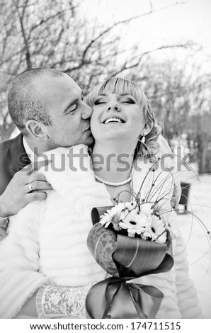 Romantic kiss happy bride and groom on winter wedding day