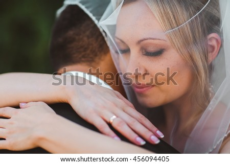 Romantic kissing bride and groom close up portrait under white veil on their wedding day outdoors.