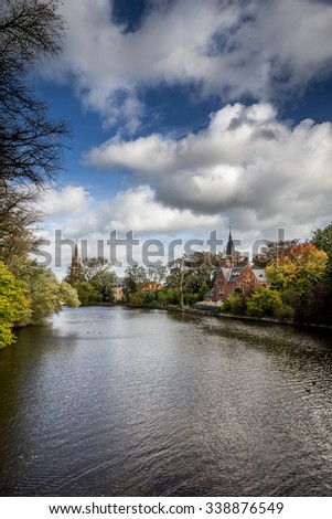 Romantic lake Minnewater in Autumn with its famous house with towers and Church Of Our Lady in Bruges, Belgium. Vertical view.  - stock photo