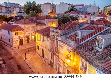 Romantic Lisbon street with the typical old buildings and new buildings - stock photo