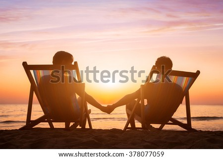 romantic love background, honeymoon, couple relaxing on the beach at sunset - stock photo