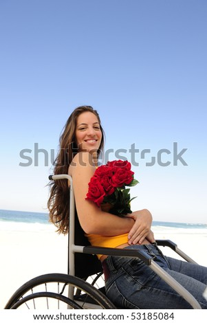 romantic love: happy woman in wheelchair with red roses - stock photo