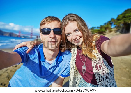 Romantic loving couple making selfie on Baker beach in San Francisco, California, USA. Golden gate bridge in the background - stock photo