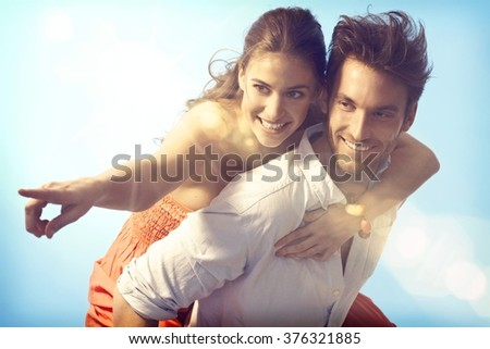 Romantic loving couple piggyback on summer holiday. - stock photo