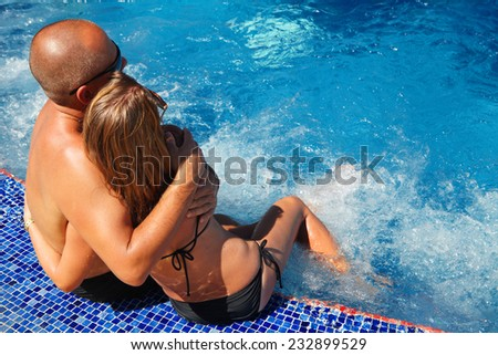 Romantic loving couple relaxing near pool. Summer vacation - stock photo