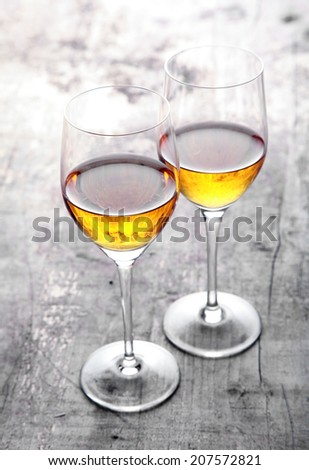 Romantic lunch for two in the garden with a pair of wineglasses with white wine standing with their bowls touching on a rustic wooden outdoor table in sunlight - stock photo