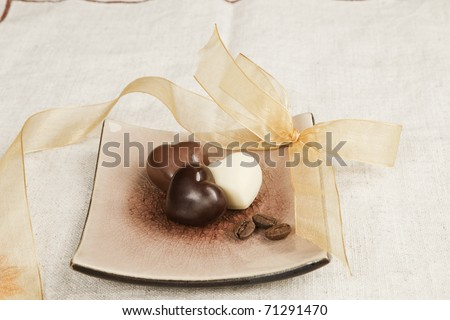 Romantic luxurious chocolate heart shaped candy variation with golden ribbon. - stock photo