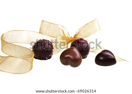 Romantic luxurious chocolate heart variation with golden ribbon on white background. - stock photo